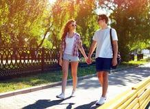Pares jovenes bastante modernos en el amor que camina en día de verano soleado Fotos de archivo