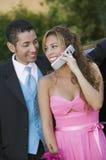 Pares jovenes bien vestidos usando el teléfono celular afuera Foto de archivo