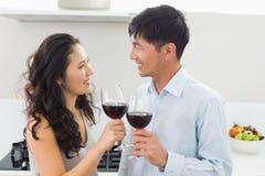Pares jovenes cariñosos con las copas de vino en cocina Imágenes de archivo libres de regalías