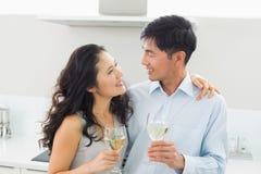 Pares jovenes cariñosos con las copas de vino en cocina Foto de archivo