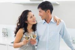 Pares jovenes cariñosos con las copas de vino en cocina Fotografía de archivo libre de regalías