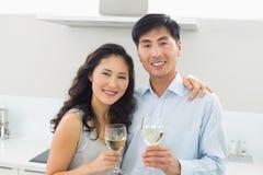 Pares jovenes cariñosos con las copas de vino en cocina Fotografía de archivo