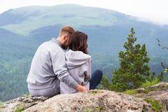 Pares jovenes cariñosos del inconformista que se sientan en una montaña, un abrazo y un l Imagenes de archivo
