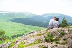 Pares jovenes cariñosos del inconformista que se sientan en una montaña, un abrazo y un l Fotografía de archivo libre de regalías