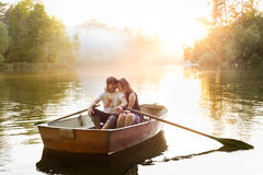 Pares jovenes cariñosos en barco en el lago que tiene tiempo romántico Imagen de archivo
