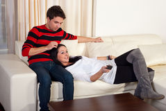 Pares jovenes cariñosos en el sofá Imagen de archivo