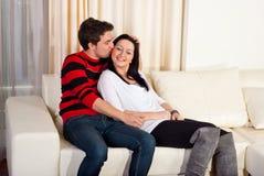 Pares jovenes cariñosos en hogar del sofá Imagenes de archivo