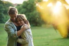 Pares jovenes cariñosos que abrazan el exterior en la puesta del sol Imagen de archivo libre de regalías