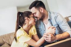 Pares jovenes cariñosos que abrazan y que se relajan en el sofá Imágenes de archivo libres de regalías