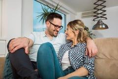 Pares jovenes cariñosos que abrazan y que se relajan en el sofá Imagen de archivo libre de regalías