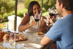 Pares jovenes cariñosos que beben el vino rojo en el lagar Imagenes de archivo