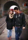 Pares jovenes cariñosos que caminan en una calle Foto de archivo