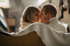 Pares jovenes cariñosos que se besan en el sofá Foto de archivo