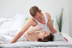 Pares jovenes cariñosos que se relajan en su cama Imagenes de archivo