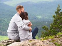 Pares jovenes cariñosos que se sientan en una montaña, abrazando y mirando a Foto de archivo