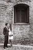 Pares jovenes cariñosos fuera de un edificio de ladrillo viejo Imagen de archivo