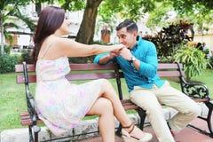 Pares jovenes cariñosos que ligan mientras que se sienta en un banco de parque Imagen de archivo