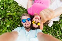 Pares jovenes caucásicos alegres que toman el selfie que miente en una hierba en un parque verano Imágenes de archivo libres de regalías