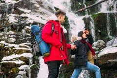 pares jovenes cerca de un invierno de la cascada Fotografía de archivo
