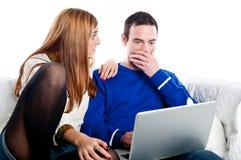 Pares jovenes chocados mientras que mira el ordenador portátil Fotografía de archivo libre de regalías