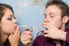 Pares jovenes con cigarrillos Foto de archivo