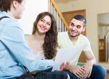 Pares jovenes con el agente de seguro Fotografía de archivo libre de regalías
