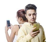 Pares jovenes con el apego del teléfono Fotografía de archivo libre de regalías