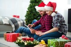 Pares jovenes con el GIF en línea de la Navidad de los sombreros de Santa Claus que hace compras Foto de archivo libre de regalías
