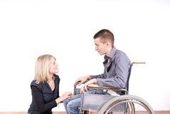 Pares jovenes con el hombre en sillón de ruedas Foto de archivo