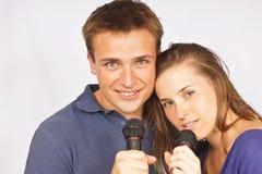 Pares jovenes con el micrófono Foto de archivo libre de regalías