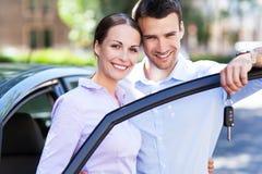 Pares jovenes con el nuevo coche Fotografía de archivo libre de regalías