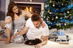 Pares jovenes con el perrito en Navidad imagenes de archivo
