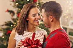 Pares jovenes con el presente sobre el árbol de navidad fotografía de archivo