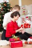 Pares jovenes con el regalo delante del árbol de navidad Fotos de archivo libres de regalías