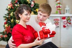 Pares jovenes con el regalo delante del árbol de navidad Imagen de archivo libre de regalías