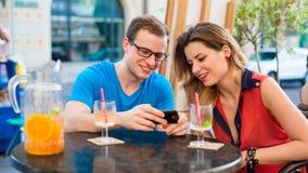 Pares jovenes con el teléfono móvil en café. Fotos de archivo