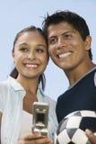 Pares jovenes con el teléfono móvil y el balón de fútbol Imagen de archivo libre de regalías