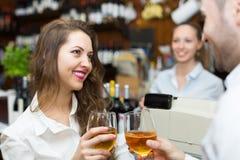 Pares jovenes con el vino en la barra Imagen de archivo libre de regalías