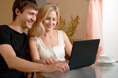 Pares jovenes con la computadora portátil Imagenes de archivo
