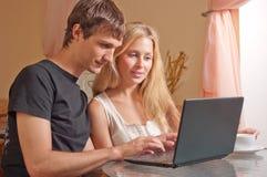 Pares jovenes con la computadora portátil Imagen de archivo