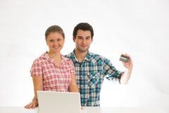 Pares jovenes con la computadora portátil Fotografía de archivo libre de regalías