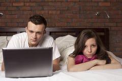 Pares jovenes con la computadora portátil. Mujer enojada fotos de archivo libres de regalías
