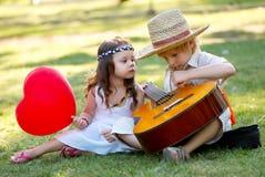 Pares jovenes con la guitarra en hierba Fotografía de archivo libre de regalías