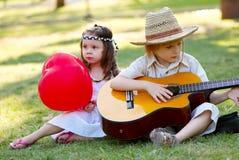 Pares jovenes con la guitarra en hierba Foto de archivo
