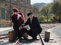 Pares jovenes con la maleta del vintage en los trainlines listos para a Foto de archivo