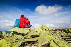 Pares jovenes con la mochila que se relaja en las montañas Alpinismo, forma de vida sana fotos de archivo