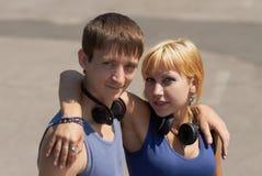 Pares jovenes con la presentación de los auriculares Imágenes de archivo libres de regalías