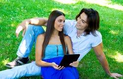 Pares jovenes con la tableta Foto de archivo libre de regalías