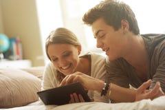 Pares jovenes con la tableta Imagen de archivo