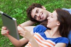 Pares jovenes con la tableta digital que miente en hierba Foto de archivo libre de regalías